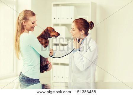 medicine, pet, animal, health care and people concept - happy woman holding dachshund and veterinarian doctor with stethoscope checking dog heartbeat at vet clinic