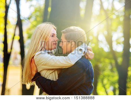 Young couple kissing in autumn park . Loving couple kissing in the sun in autumn park. Kissing in sun.
