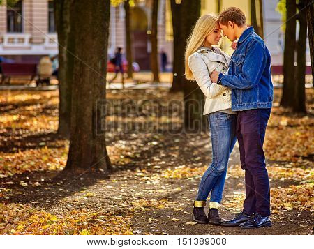 Young couple in love kissing in autumn park . Loving couple kissing in sun in autumn park. Autumn city background.