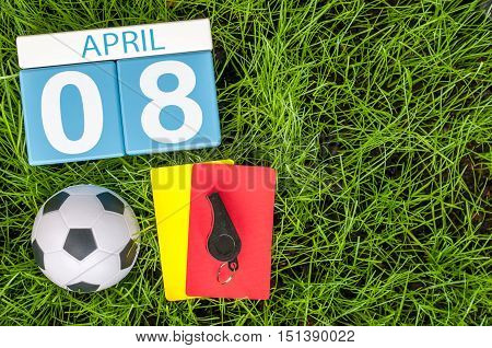 April 8th. Day 8 of month, calendar on football green grass background with soccer outfit. Empty space for text.