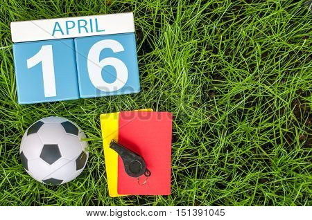 April 16th. Day 16 of month, calendar on football green grass background. Spring time, empty space for text.