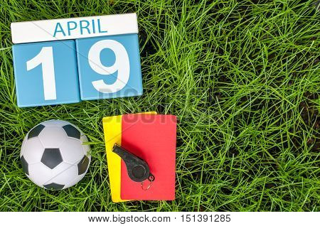 April 19th. Day 19 of month, calendar with football green grass background. Spring time