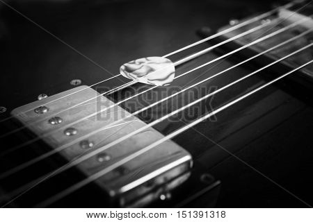 Acoustic guitar with plectrum close up in dark background
