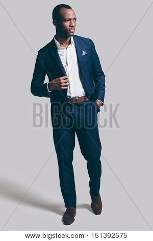 Confident and stylish. Full length of handsome young African man in full suit adjsuting his jacket and holding one hand in pocket while standing against grey background