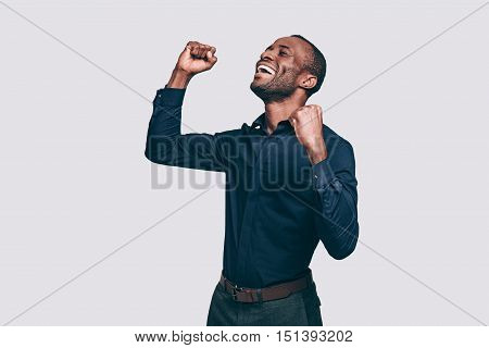 Feeling so happy! Happy young African man gesturing and keeping eyes closed while standing against grey background
