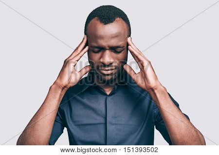 This is too much! Frustrated young African man touching head with hands and keeping eyes closed while standing against grey background
