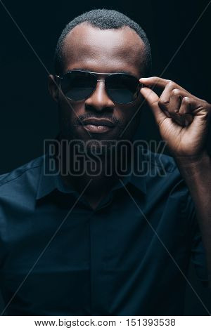 Cool and trendy. Portrait of handsome young African man while being in front of black background