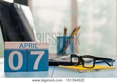 April 7th. Day 7 of month, calendar on business office background, workplace with laptop and glasses. Spring time, empty space for text.