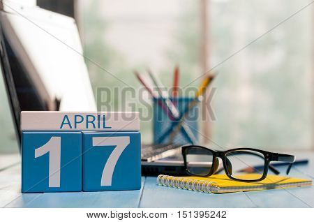 April 17th. Day 17 of month, calendar on business office background, workplace with laptop and glasses. Spring time, empty space for text.