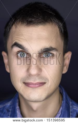 Amusing macro portrait of a young guy on the dark background. He grimaces and looks into the camera with a smile. Vertical.