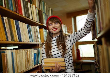 Young student girl choosing books between the shelves in the library