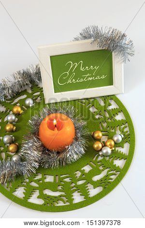 Merry Christmas greeting card on green christmas mat silver tinsel with silver and golden christmas balls and orange candle against white background horizontal top view