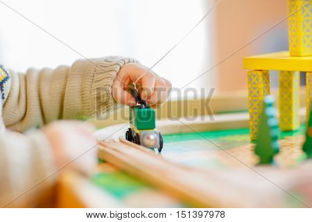 Little toddler playing with wooden toy, indoors. Hand of child with train. Close up, lifestyle, game and education.