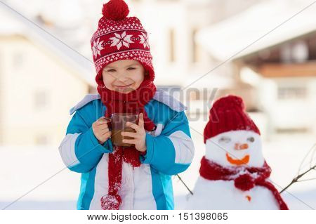 Happy Beautiful Child Building Snowman In Garden, Winter Time, Holding Cup Of Hot Tea