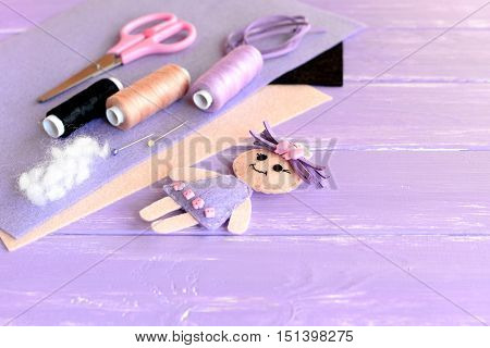 Creative art and craft idea for children. Felt doll, scissors, thread, needles, pins, suede cord, felt sheets on wooden background with empty place for text. Set to create children toy