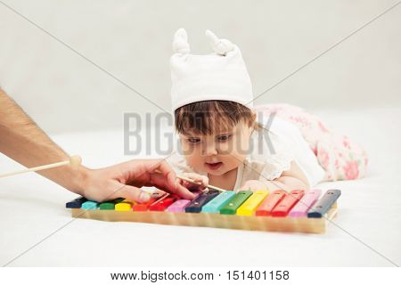 Baby girl playing with xylophone toy on blanket at home
