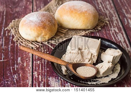 Yeast, fresh and dry granulated, on black ceramic plate, next to two freshly baked buns.