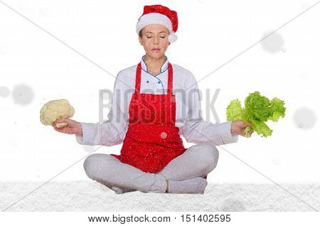 cook in Santa hat yoga vegetables under snow on white background