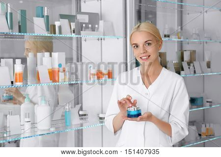 Cosmetologist holding cream beside showcases