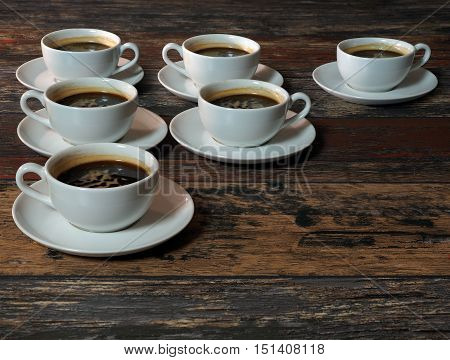 Many identical white cups of coffee on the old wooden boards