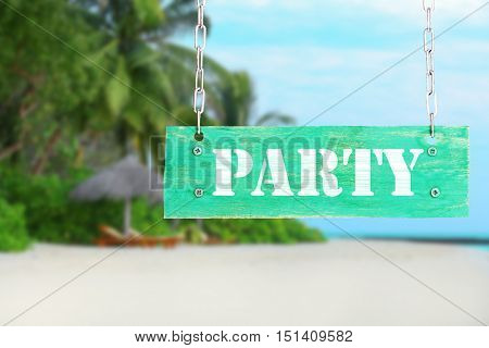 Wooden sign with text PARTY on tropical beach and blue sky background