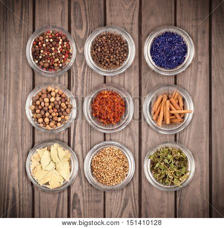 Various spices on a wooden background .