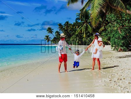 Young family with two kids walking at tropical beach, family beach vacation
