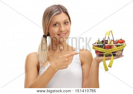Joyful woman holding a small shopping basket full of fruits and vegetables wrapper with measuring tape and pointing isolated on white background