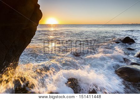 Ocean tide rushing over the rocks as sunrises at Burleigh Heads Gold Coast.