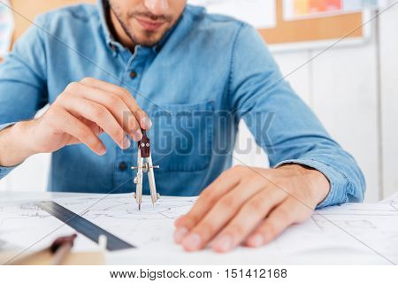 Cropped image of a architect working on construction blueprint in office with divider at office