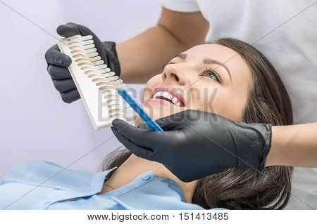 Delightful girl in a blue shirt in the dentist's office. Doctor in black gloves makes comparison of the patient teeth with the dental whitening chart. Close-up photo. Horizontal.