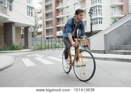 A guy in a blue denim jacket goes to school on an orange bike. Cyclists on the road in the city. Stylish student with a backpack