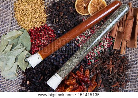 Different Spices And Condiments And Seasoning In Tubes On Sackcloth Background