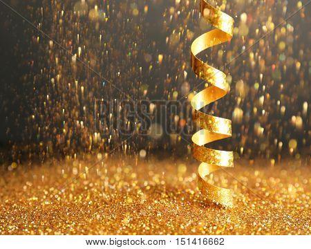 Shiny golden streamer and glitter on dark background