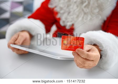 Santa Claus with credit card and tablet at home, closeup