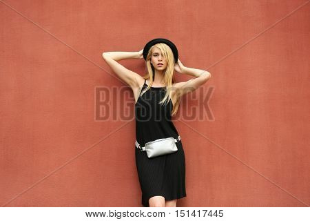 Young woman in black dress with silver clutch on brown background