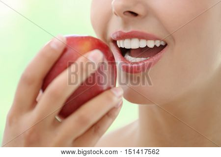 Young woman eating red apple, close up