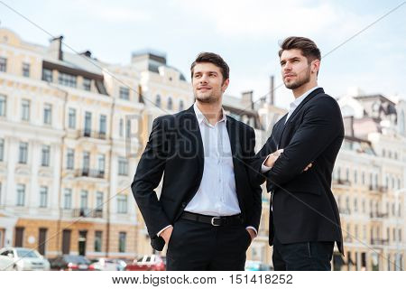 Two confident successful young businessmen standing outdoors