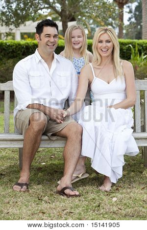 Happy Mother Father Daughter Family Sitting On Park Bench
