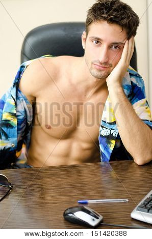 Attractive, fit young man with his shirt open sitting at office desk barechested thinking about vacation