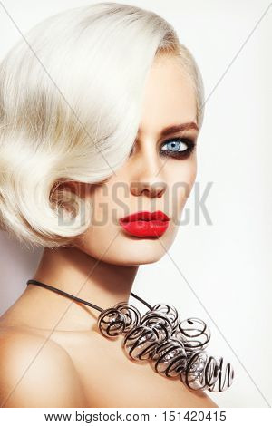 Close-up portrait of young beautiful woman with stylish smoky eye red lips make-up and fancy glass necklace