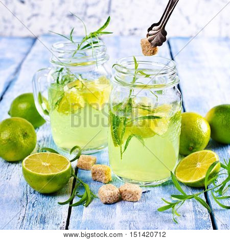 Drink of lime and tarragon in a glass on a wooden background. Selective focus.