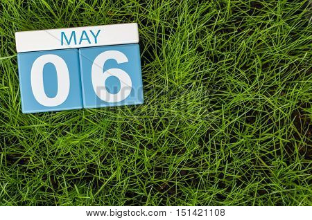 May 6th. Day 6 of month, wooden color calendar on football green grass background. Spring time, empty space for text.