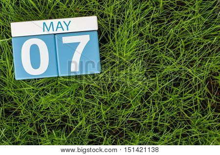 May 7th. Day 7 of month, calendar on football green grass background. Spring time, empty space for text.
