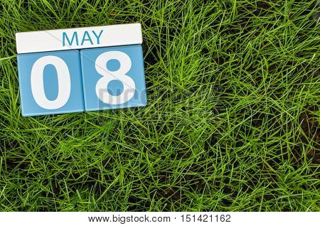 May 8th. Day 8 of month, calendar on football green grass background. Empty space for text.