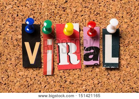 The word Viral in magazine letters pinned to a cork notice board. Viral is often used to describe an image,video or product that is widely circulated on the internet