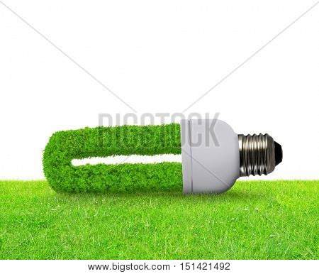 Eco light bulb in grass on white background - Green energy concept.
