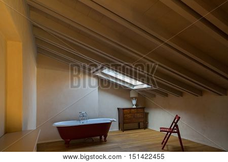 Red bathtub placing under the window in the attic room, next to red wooden chair, old vintage style