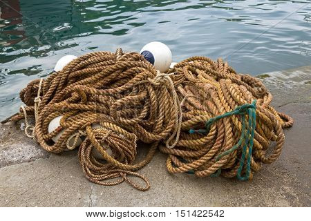 Big pile of ropes with floats to tie boats and used in fishing industry by Mediterranean Sea in Italy, southern Europe