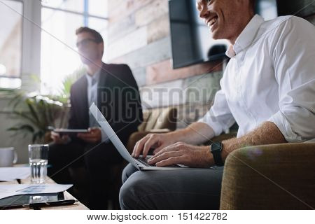 Businessman Using Laptop In Meeting With Corporate Colleagues
